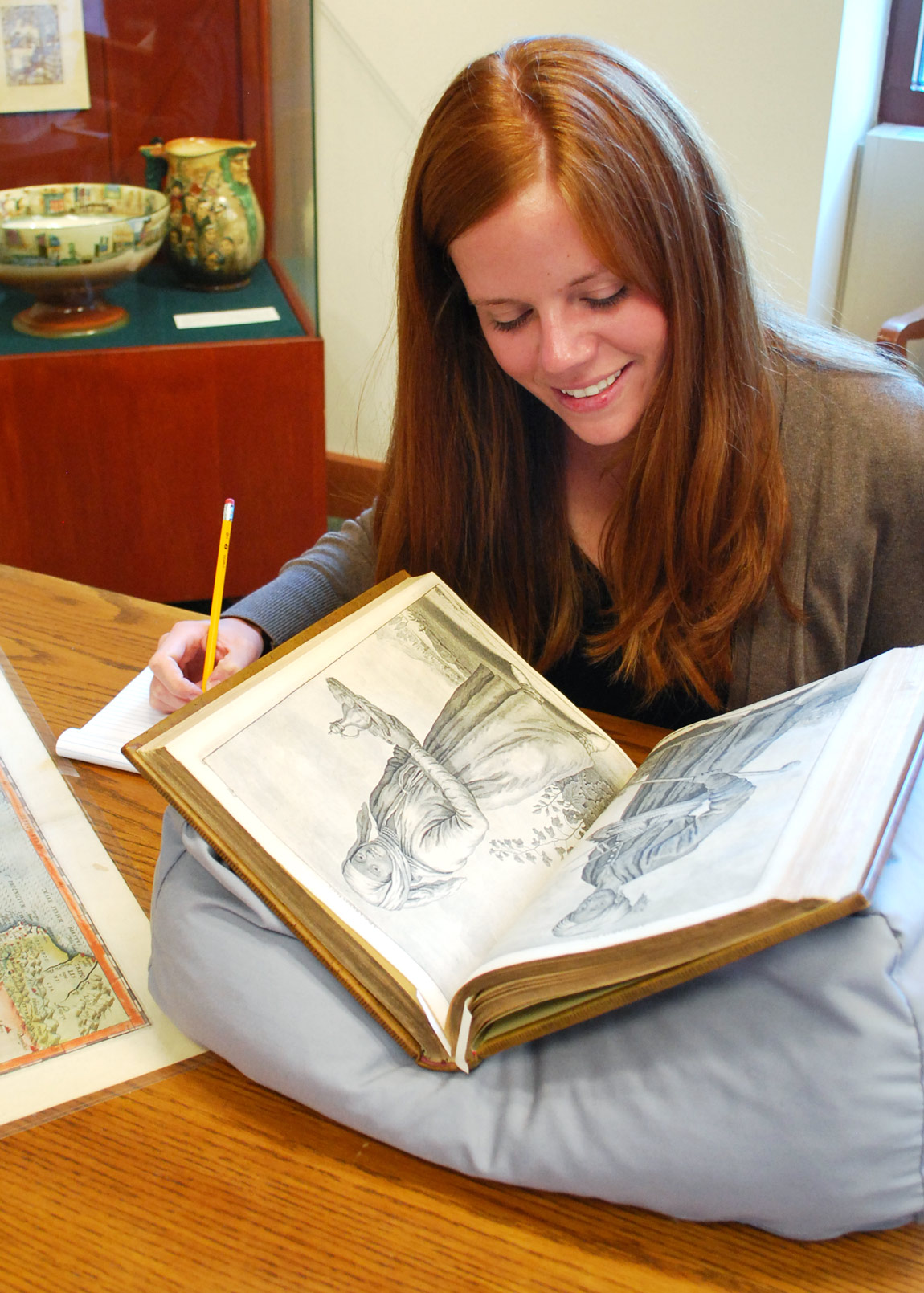 Student looking through a special collections book.