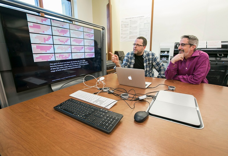 Photo of two professors viewing a presentation in the Scholar's Lab.