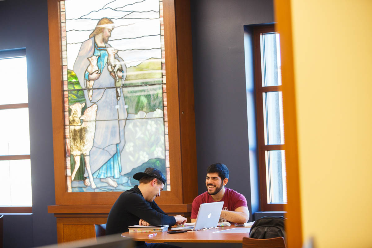 Photograph of two students talking near the stained glass portrait of St. Vincent de Paul in the JTR Library