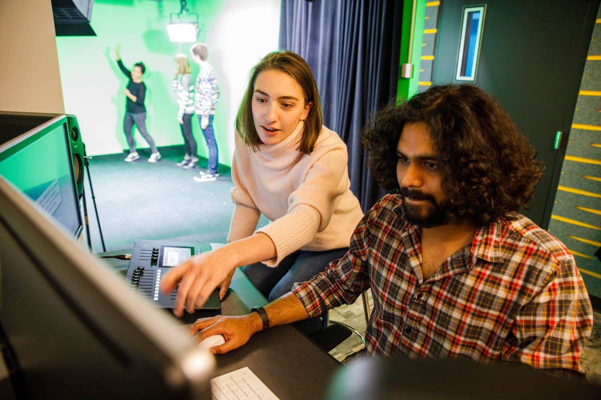 Students working at a computer with students performing in front of a green screen in the background.